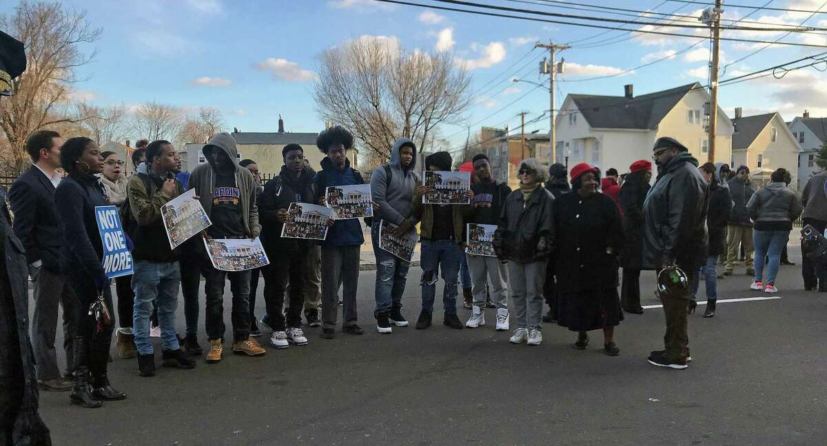 Some of the youth that gathered in Bridgeport, Conn., Friday evening carried signs. Some signs showed the faces of victims of gun violence. One woman carried a sign that said
