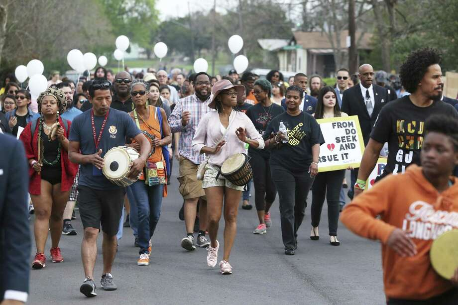 Eastside community members hold a peace march Friday through neighborhood streets leading to the home on Oldfort Hill where Draylen Mason, 17, was killed by a package bomb earlier this week. Photo: Tom Reel / Tom Reel / San Antonio Express-News / 2017 SAN ANTONIO EXPRESS-NEWS
