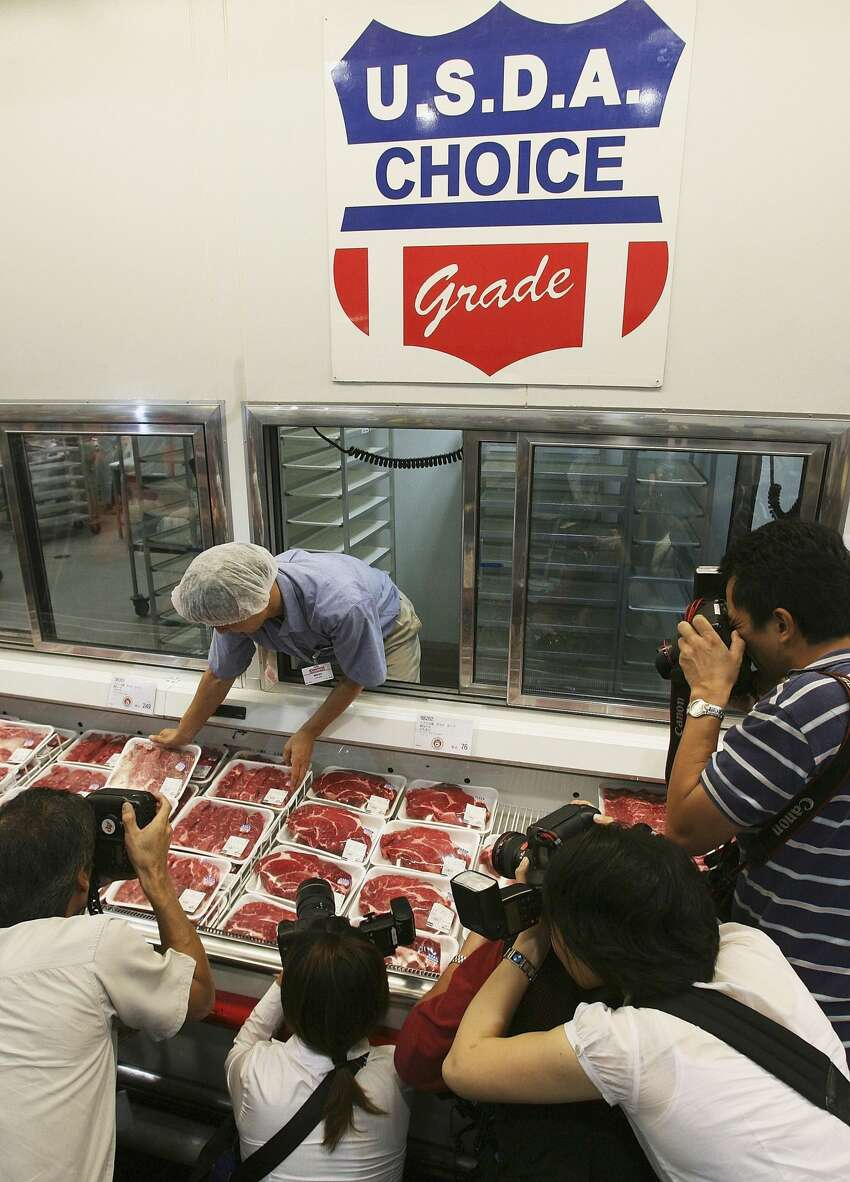 CHIBA, JAPAN - AUGUST 9: Photographers take pictures as a worker sets-up a display of U.S. beef products at a branch of U.S. owned supermarket Costco on August 9, 2006 in Chiba, Japan. The Japanese government lifted the ban on the import of U.S. beef on July 27, and the first shipment of cargo, which faced seperate inspections from both the Japanese Health Ministry and Agriculture Ministry, arrived on August 7. The ban had been in place since January 20, when inspectors found banned material in a shipment of veal from a U.S. supplier, just two months after lifting a previous two year import ban. (Photo by Koichi Kamoshida/Getty Images)