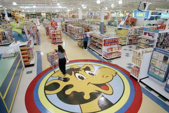 FILE- In this July 30, 1996, file photo, a woman pushes a shopping cart over a graphic of Toys R Us mascot Geoffrey the giraffe at the Toys R Us store in Raritan, N.J. Toys R Us CEO David Brandon told employees Wednesday, March 14, 2018, that the company's plan is to liquidate all of its U.S. stores, according to an audio recording of the meeting obtained by The Associated Press. (AP Photo/Daniel Hulshizer, File)