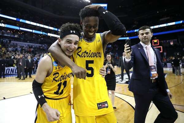 CHARLOTTE, NC - MARCH 16:  K.J. Maura #11 and teammate Jourdan Grant #5 of the UMBC Retrievers celebrate their 74-54 victory over the Virginia Cavaliers during the first round of the 2018 NCAA Men's Basketball Tournament at Spectrum Center on March 16, 2018 in Charlotte, North Carolina.  (Photo by Streeter Lecka/Getty Images)