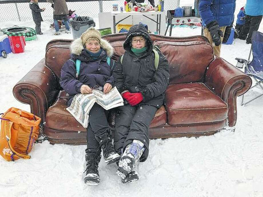 "Laurie Beavers and her friend, Kathy Burkholder, both of Greenfield, ""chill"" on a couch at the beginning of the Iditarod race ceremonial start. Photo: Photo Provided"