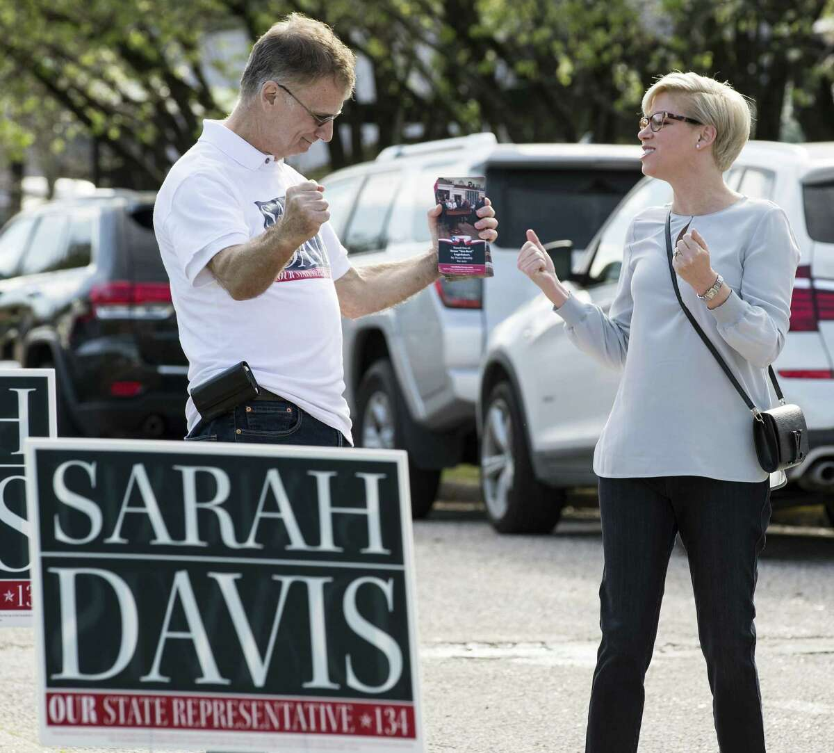 State Rep. Sarah Davis, R-Houston, speaks to campaign volunteer Michael Sternesky, left, before voting Tuesday in in Houston. Davis won despite support for her opponent from Governor Greg Abbott.