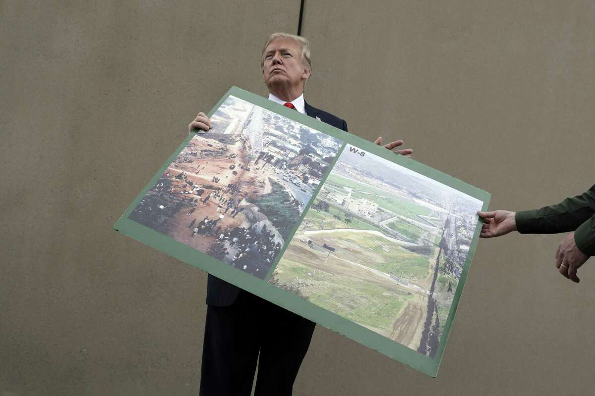 President Donald Trump holds a photo of the border area as he reviews border wall prototypes on March 13 in San Diego. Rodney Scott, the Border Patrol's San Diego sector chief, helps to hold the print.