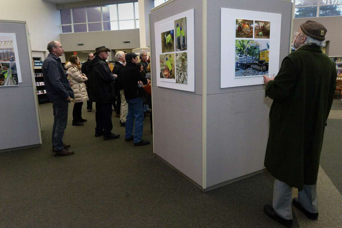 Bridgeport resident Joseph Celli looks at the artwork during a reception for the newly installed exhibit in the Library's Great Hall, Transforming The Westport Library, Friday, March 16, 2018, which showcases renderings of the planned renovation by architect Henry Myerberg's New York-based design firm, HMA2, paired with photographs of current construction on the Library's first floor by Westport photographer Richard Frank at the library in Westport, Conn.