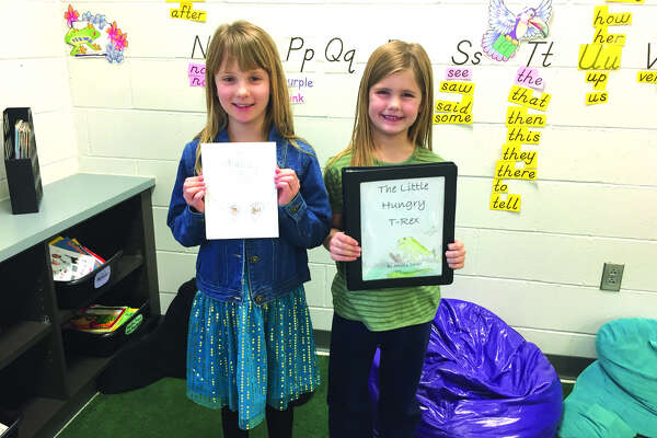 "Hamel Elementary School Young Authors representatives are, from left:  first grader Jessica Sever (state representative), who wrote ""The Little Hungry T-Rex"" and second grader Sydney Baugh (county representative), who wrote ""The Sparkling Eyes."""