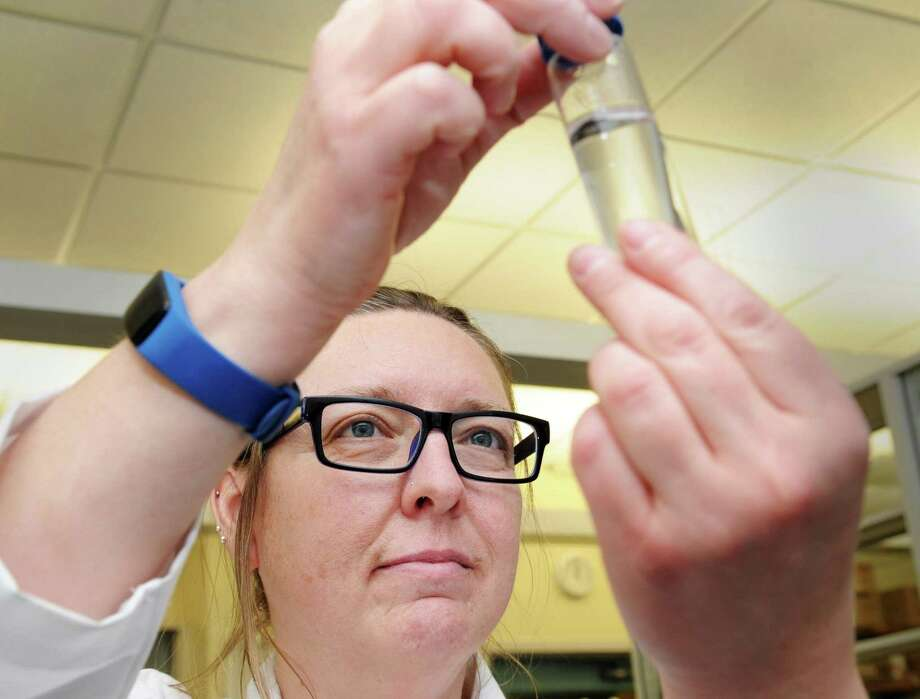 Stephanie Kexel, a UConn lab manager, displays a Connecticut river water sample she was analyzing in the lab at the UConn's Center for Environmental Sciences and Engineering, Storrs, Conn., Wednesday, March 14, 2018. There is a fundraiser getting kicked off to raise money for an endowment fund to set-up Innis Arden Cottage at Greenwich Point as a major research center, led by UConn scientists, to study Western Long Island Sound. Photo: Bob Luckey Jr. / Hearst Connecticut Media / Greenwich Time