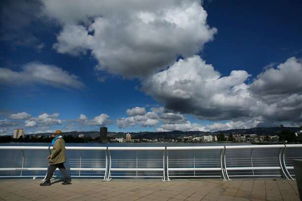 People take advantage of a break in the rain for a stroll around Lake Merritt, as seen Wed. March 14, 2018, in Oakland, Calif.