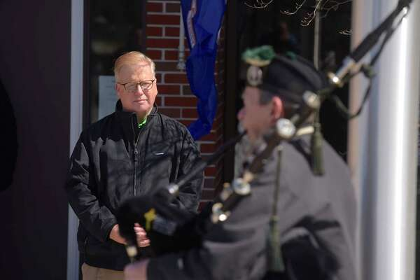 Mayor Mark Boughton watches as Peter Hearty from the Celtic Cross Pipe & Drum of Danbury, plays the bag pipes during the raising of the Irish flag at Danbury City Hall on Saturday afternoon, March 17, 2018, in Danbury, Conn.