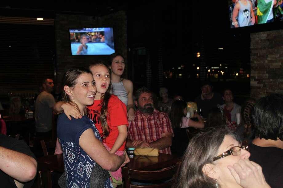 "Barclay Stockett holds her niece,Austen Martin, as they watch the March 15 episode of ""American Ninja Warrior: Ninja V. Ninja"" at Three B's Grill in Kingwood. Photo: Melanie Feuk"