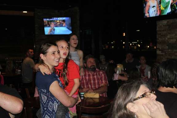 "Barclay Stockett holds her niece, Austen Martin, as they watch the March 15 episode of ""American Ninja Warrior: Ninja V. Ninja"" at Three B's Grill in Kingwood."