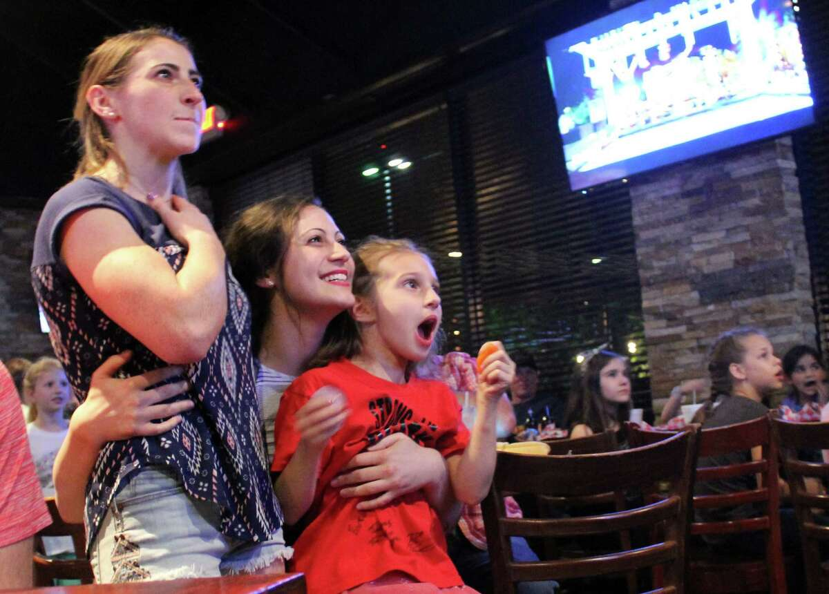 Barclay Stockett, her sister Sidney Stockett, and their niece Austen Martin embrace as they watch the final round of