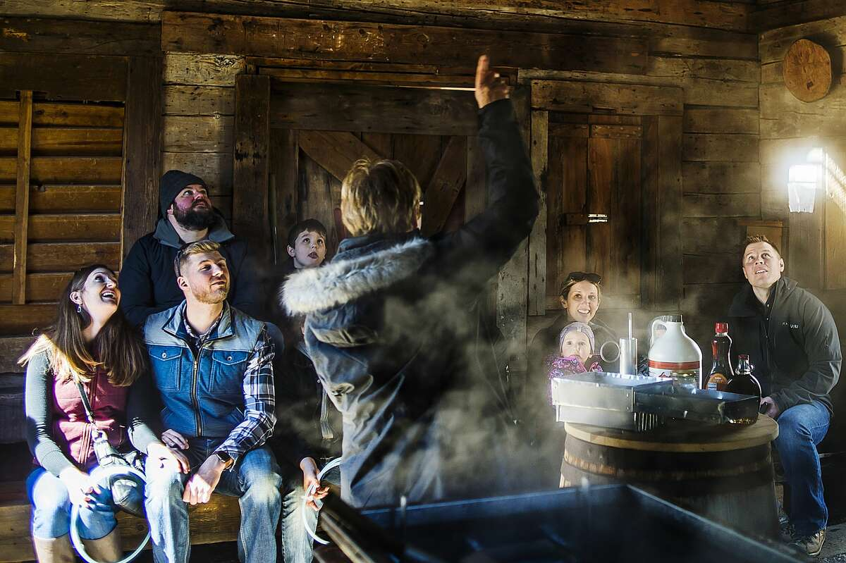 People listen as Sue Burtch explains how sap is boiled down into syrup inside the sugarhouse during Maple Syrup Day on Saturday, March 17, 2018 at the Chippewa Nature Center. (Katy Kildee/kkildee@mdn.net)