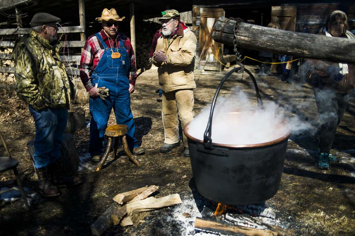Volunteers keep watch of a large kettle, the likes of which can be used to boil sap into syrup, during Maple Syrup Day on Saturday, March 17, 2018 at the Chippewa Nature Center. (Katy Kildee/kkildee@mdn.net)