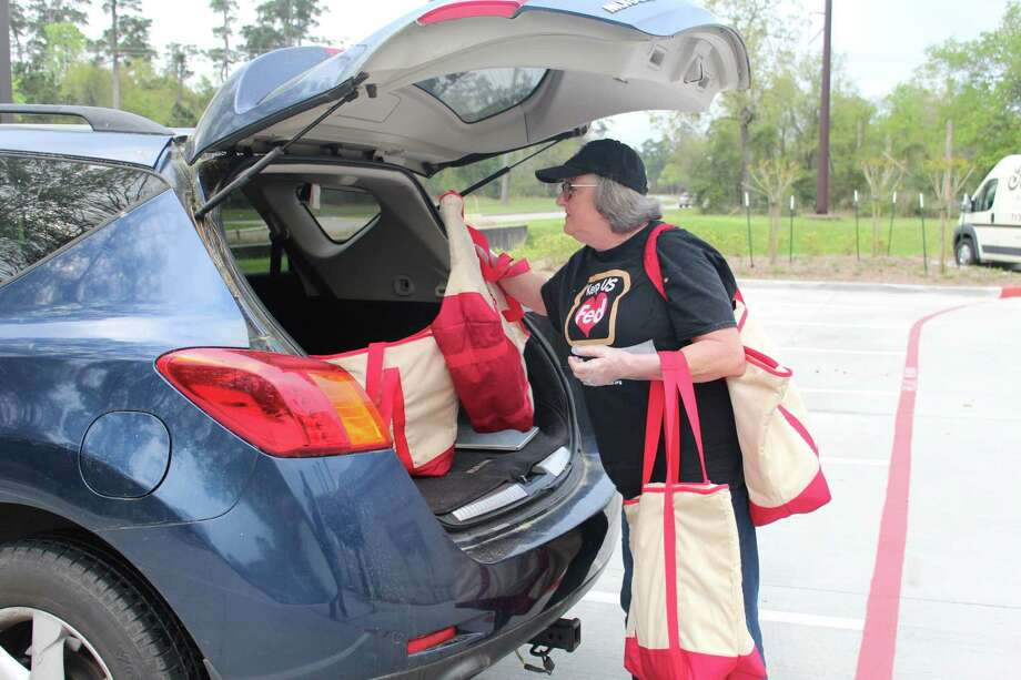 Eileen Walton, a volunteer with Keep US Fed, picks up cooked meat from Goode Company in The Woodlands on Friday, March 16, and loads it into her vehicle for delivery to a local nonprofit. Photo: Staff Photo By Patricia Dillon