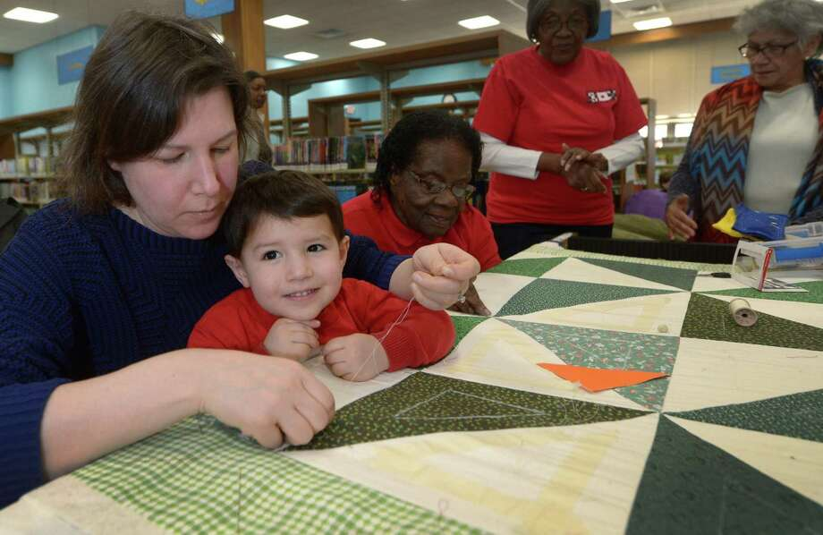 Elizabeth Londono and her son, James Londono, 3, help the Peace by Piece quilters during their quilting bee while at the Norwalk Library to celebrate the groups 10th anniversay and dedicate the recently hung quilts in the library's Children's Room in Norwalk, Conn. Photo: Erik Trautmann / Hearst Connecticut Media / Norwalk Hour