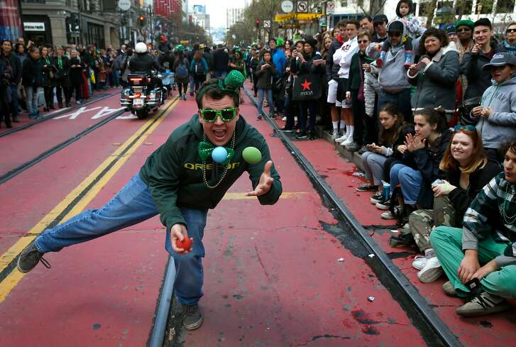 Juggler Jacob Graham performs for a large crowd gathered on Market Street to watch the 167th St. Patrick's Day Parade in San Francisco, Calif. on Saturday, March 17, 2018.