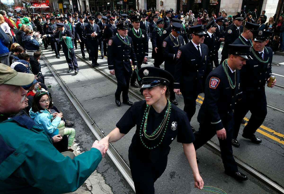 Doug Floyd (left) greets a firefighter marching in the 167th St. Patrick's Day Parade in San Francisco, Calif. on Saturday, March 17, 2018.