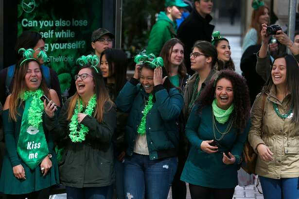 Crowd members laugh and smile as a contingent from the U.S. Coast Guard marches past in the 167th St. Patrick's Day Parade in San Francisco, Calif. on Saturday, March 17, 2018.
