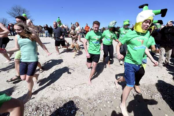 Leapers run into the Long Island Sound for the Leprechaun Leap at Walnut Beach in Milford on March 17, 2018.  The event raised money for the Literacy Volunteers of Southern Connecticut.
