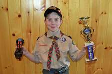 First place winner Austin Sciulla with his winning car and trophy at the Pinewood Derby Championship at Seton Scout Reservation in Greenwich.