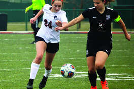 Edwardsville sophomore Rileigh Kuhns, left, battles for the ball with Belleville West midfielder Addison Hanusek during the first half of Saturday's game inside the District 7 Sports Complex.