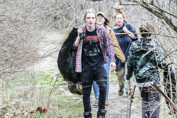 A line of volunteers carry trash bags filled with litter collected from the reaches of Piasa Park in Alton. More than 50 people set out to pick the park clean Saturday morning to honor the memory of Trinity Buel, a 17-year-old killed Feb. 19 in a traffic accident.