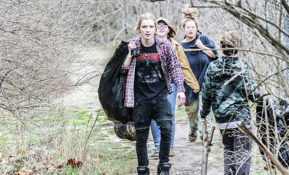 A line of volunteers carry trash bags filled with litter collected from the reaches of Piasa Park in Alton. More than 50 people set out to pick the park clean Saturday morning to honor the memory of Trinity Buel, a 17-year-old killed Feb. 19 in a traffic accident. Photo: Nathan Woodside | For The Telegraph