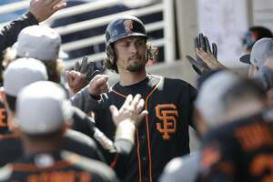 San Francisco Giants' Jarrett Parker is greeted in the dugout after his solo home run during the fourth inning of a spring training baseball game against the Milwaukee Brewers, Wednesday, Feb. 28, 2018, in Maryvale, Ariz. (AP Photo/Carlos Osorio)