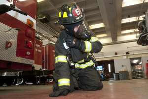 """Bridgeport firefighter Justin Fontan takes part in a """"mayday"""" drill at fire headquarters in Bridgeport, Conn. March 9, 2018. During the drill, firefighters dressed in full protective gear learn to communicate their condition and location via a radio in their breathing apparatus in the event they become stranded or incapacitated during an emergency situation."""