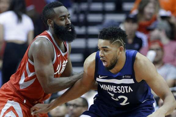 Minnesota Timberwolves center Karl-Anthony Towns (32) looks to drive around Houston Rockets guard James Harden (13) during the second half of an NBA basketball game Friday, Feb. 23, 2018, in Houston. (AP Photo/Michael Wyke)