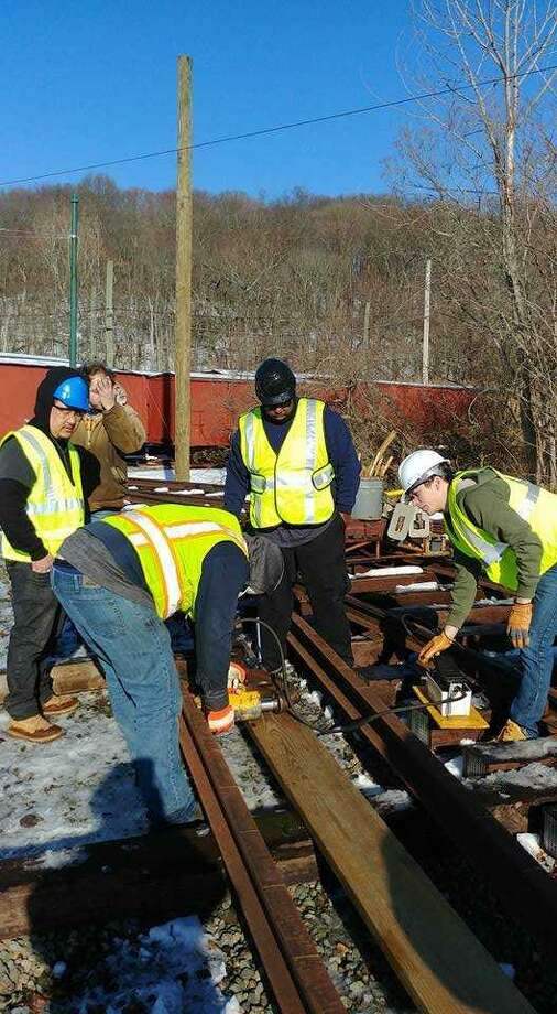 Gateway Community College students Avery Blank, Jeff Hackner, Shannon Denny, Kunga Chodek and Keith DeCosta apply their skills on a stretch of railroad in an undated photo. Photo: Contributed Photo