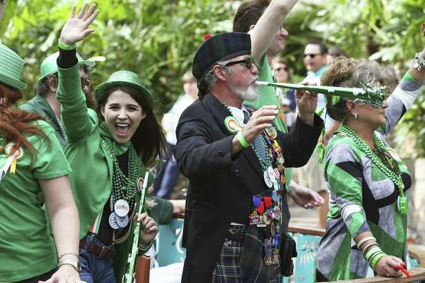 Green clad barge riders move down the river in float 3 as revelers take to the Riverwalk for St. Patrick's Day on March 17, 2018.