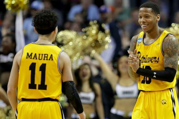 CHARLOTTE, NC - MARCH 16:  Jairus Lyles #10 congratulates teammate K.J. Maura #11 of the UMBC Retrievers after their 74-54 victory over the Virginia Cavaliers during the first round of the 2018 NCAA Men's Basketball Tournament at Spectrum Center on March 16, 2018 in Charlotte, North Carolina.  (Photo by Streeter Lecka/Getty Images)