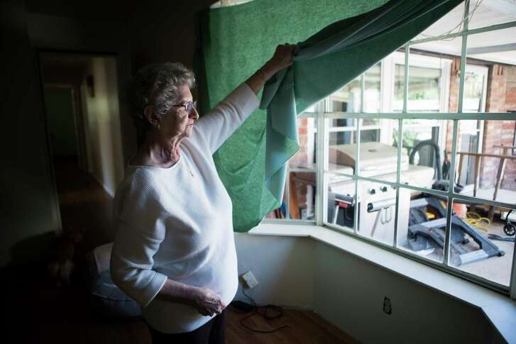 Gloria Bullock, 78, lifts her table linen substituting her flood damaged curtains at her home, Monday, March 12, 2018, in Bear Creek Village. Bullock and her husband, with the help of the community has been working hard trying to get their home functional after it got flooded.