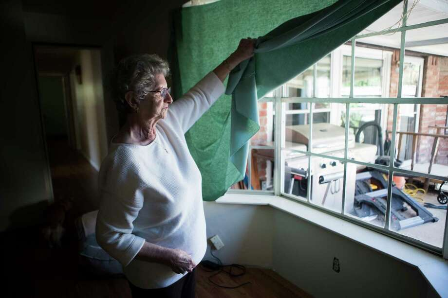 Gloria Bullock, 78, lifts her table linen substituting her flood damaged curtains at her home, Monday, March 12, 2018, in Bear Creek Village. Bullock and her husband, with the help of the community has been working hard trying to get their home functional after it got flooded. Photo: Marie D. De Jesus, Houston Chronicle / © 2018 Houston Chronicle