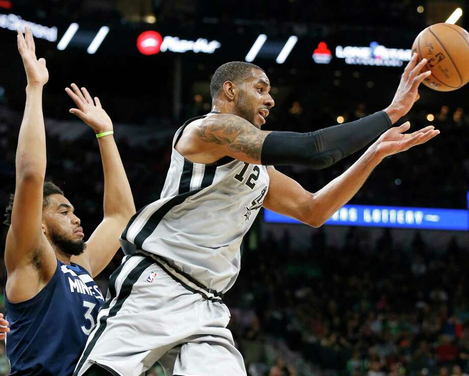 San Antonio Spurs' LaMarcus Aldridge passes around Minnesota TimberwolvesÕ Karl-Anthony Towns during first half action Saturday March 17, 2018 at the AT&T Center. Photo: Edward A. Ornelas, San Antonio Express-News / © 2018 San Antonio Express-News