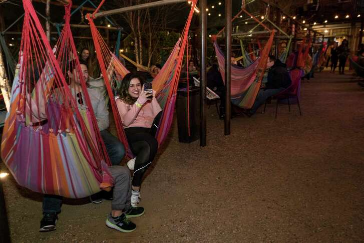Patrons sit in hammocks in the outdoor garden listening to Kermit Ruffins perform at Axelrad Beer Garden on Wednesday, March 7, 2018, in Houston.