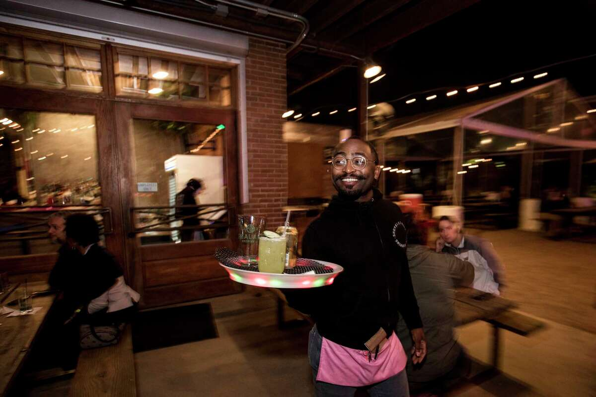 Zachary Taylor carries out a tray of drinks at Axelrad Beer Garden on Wednesday, March 7, 2018, in Houston.