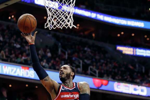 Washington Wizards forward Mike Scott (30) shoots between Indiana Pacers forward Thaddeus Young (21) and guard Cory Joseph (6) during the second half of an NBA basketball game Saturday, March 17, 2018, in Washington. The Wizards won 109-102. (AP Photo/Alex Brandon)