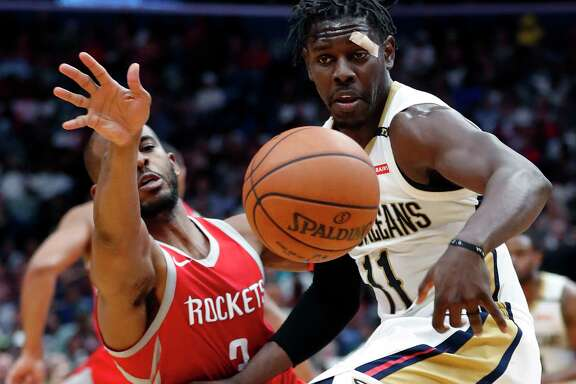 Pelicans guard Jrue Holiday, right, and Rockets guard Chris Paul battle for possession of the ball during the second half Saturday night in New Orleans.