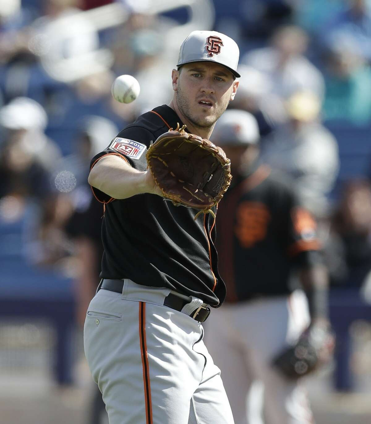 San Francisco Giants pitcher Ty Blach catches a toss from the third baseman during the third inning of a spring training baseball game against the Milwaukee Brewers, Wednesday, Feb. 28, 2018, in Maryvale, Ariz. (AP Photo/Carlos Osorio)
