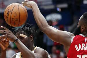 New Orleans Pelicans guard Jrue Holiday (11) loses the ball as he tries to goes to the basket between Houston Rockets guard James Harden (13) and center Clint Capela (15) during the second half of an NBA basketball game in New Orleans, Saturday, March 17, 2018. The Rockets won 107-101. (AP Photo/Gerald Herbert)