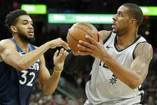 The Spurs' LaMarcus Aldridge looks for room around Minnesota's Karl-Anthony Towns during Saturday's game. Aldridge finished with 39 points and 10 rebounds as the Spurs kept their postseason hopes alive.