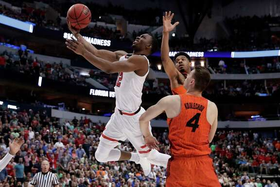 Texas Tech guard Keenan Evans (12) shoots after driving between Florida's Jalen Hudson, rear, and Egor Koulechov (4) during the second half of a second-round game at the NCAA men's college basketball tournament in Dallas, Saturday, March 17, 2018. (AP Photo/Tony Gutierrez)