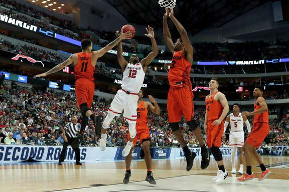 DALLAS, TX - MARCH 17:  Keenan Evans #12 of the Texas Tech Red Raiders attempts a shot between Chris Chiozza #11 and Jalen Hudson #3 of the Florida Gators in the second half during the second round of the 2018 NCAA Tournament at the American Airlines Center on March 17, 2018 in Dallas, Texas. (Photo by Tom Pennington/Getty Images)