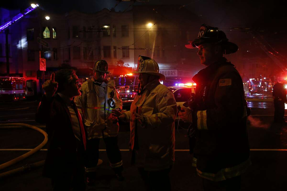 Former SF Supervisor Aaron Peskin, left, talks with SFFD Fire Chief Joanne Hayes-White, center right, during a four-alarm structure fire at the North Beach neighborhood in San Francisco, Calif. on Saturday, March 17, 2018.