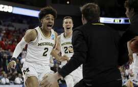 Michigan guard Jordan Poole (2) celebrates with teammates after his game-winning basket in an NCAA men's college basketball tournament second-round game against Houston, Saturday, March 17, 2018, in Wichita, Kan. Michigan defeated Houston 64-63. (AP Photo/Orlin Wagner)