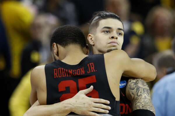 Houston guard Rob Gray hugs Houston Galen Robinson Jr. (25) after the team's NCAA men's college basketball tournament second-round game against Michigan on Saturday, March 17, 2018, in Wichita, Kan. Michigan won 64-63. (AP Photo/Charlie Riedel)