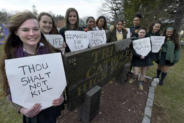 """At left, Grace Curley-Holmes, a senior at Trinity Catholic High School in Stamford, Conn., with classmates in front of the school on March 16, 2018. Trinity Catholic had a """"rosary walk"""" this past Wednesday, March 14th, to honor the Parkland victims. Students walked around school fields saying the rosary for 17 minutes as opposed to a walkout. However, 13 girls, along with Curley-Holmes, felt the need to do something more and held a walkout in the afternoon without the school's support. The students held signs, mostly religion based to honor the school."""